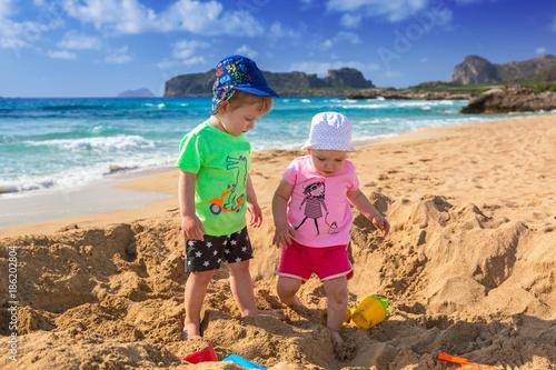 Bliźnięta bawić się w piasku na wakacje w Grecji