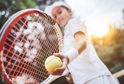 Sportowy dziewczyna, przygotowujących się do służby piłkę tenisową. Zbliżenie piękne dziewczyny Yong, trzymając piłkę tenisową i rakieta. Dziecko tenisista przygotowywał się do służby.