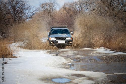 Chabarowsk, Rosja - 25 marca 2017 roku: Mitsubishi Pajero Sport na polnej drodze w początku wiosny robi plamy z kałuży