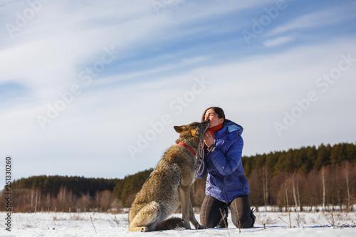 Człowiek karmi swoich psich sucharów, z ust do ust na świeżym powietrzu w okresie zimowym śnieżnej pogody.