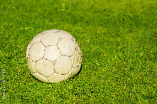 Stary wytarty piłka na zielonym trawniku
