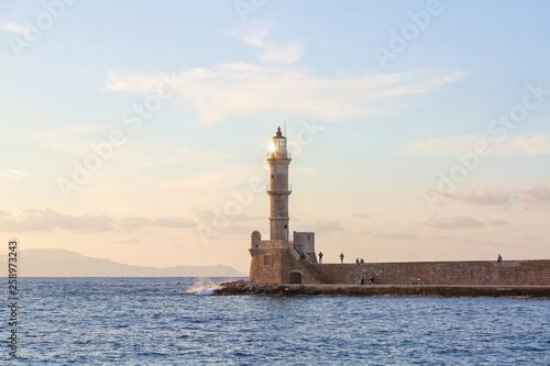Lampy zapalić latarnię w godzinach wieczornych. Starożytna architektura. Lokalizacja portu Chania, wyspa Kreta, Grecja. Zachód słońca. Krajobraz z górami i morzem.