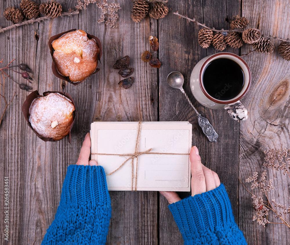 ręka w niebieskim ręcznie dzierganej swetrze, trzymając stos starych, pustych kart, związany z liny