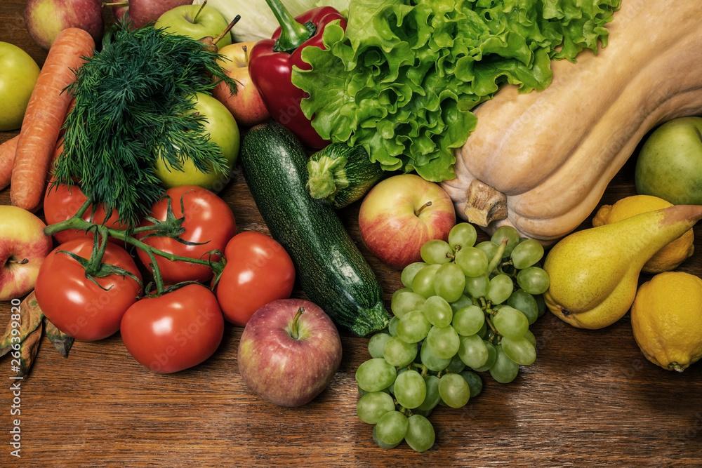 Różne świeże warzywa i owoce na drewnianym dębowym stole.