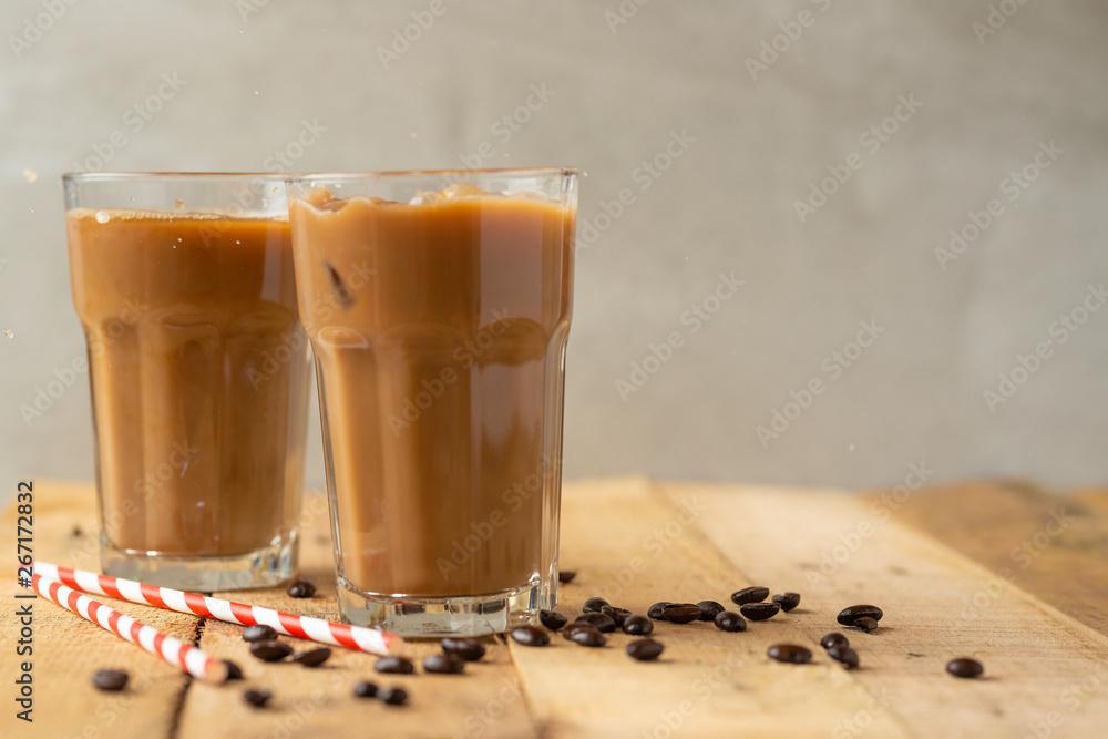 Kawa z lodem w przezroczystych szklankach z lodem i соломинками, na drewnianym tle, chłodzące napoje