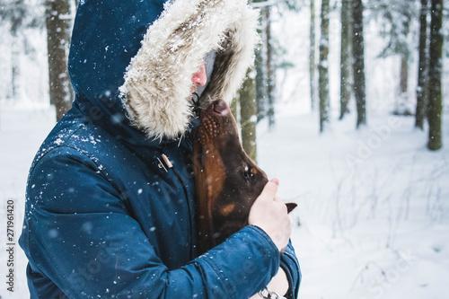 człowiek z psem w zimowym lesie