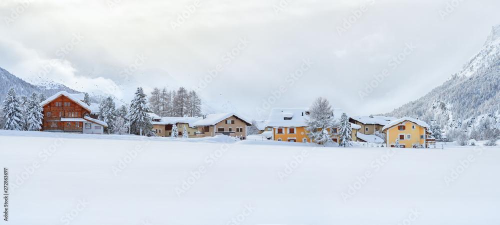 Zimowa panorama ośnieżonych krajobraz w godzinach wieczornych z kameralnych budynków w wiosce znajduje się w Szwajcarii.