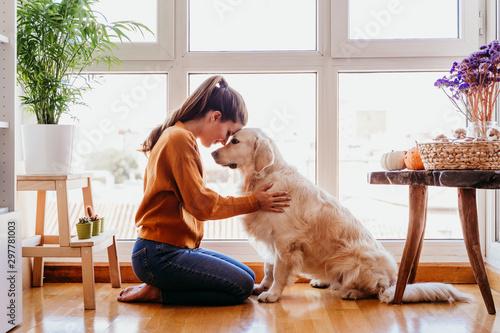 piękna kobieta przytula jej urocze golden retriever pies w domu. miłość do pojęcia zwierząt. styl życia w pomieszczeniu
