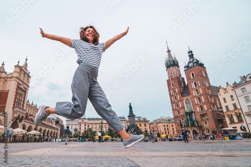 miasto pojęcie turystyka kobieta skoki w Krakowie, rynek główny, kościół mariacki na tle