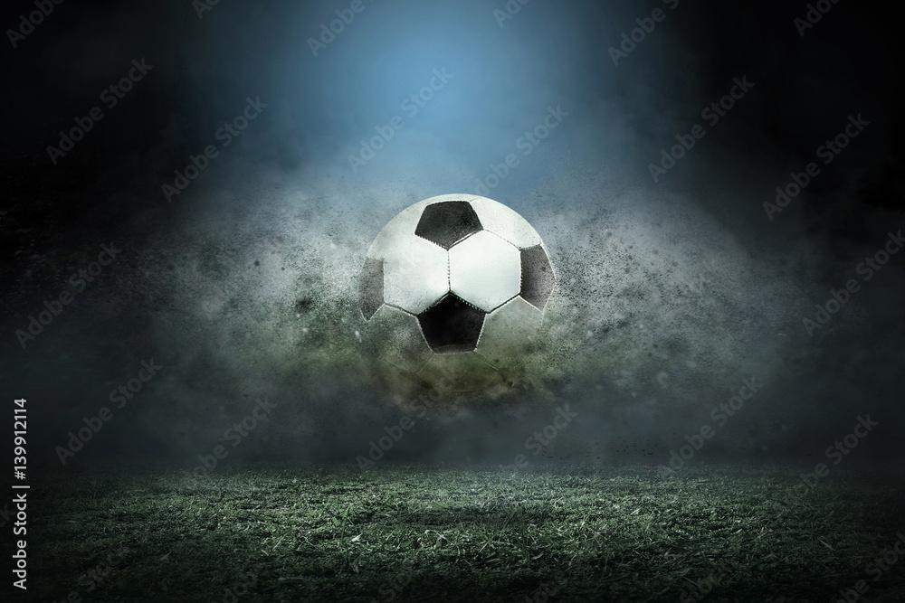 Przenoszenie piłki nożnej wokół забрызгать kropli na murawie stadionu.