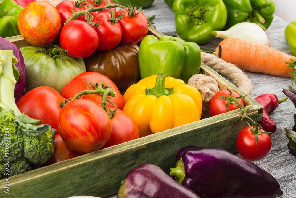Zestaw różnych świeżych, surowych warzyw w drewniana taca, jasne tło