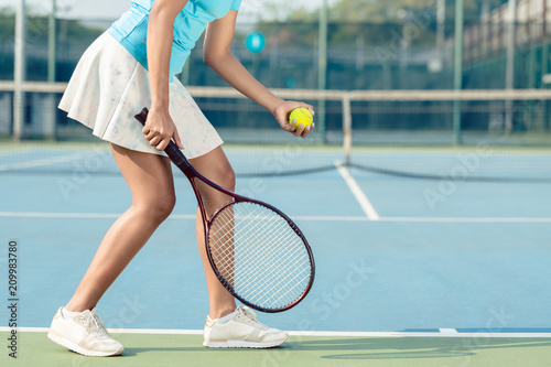 Strona niskiego przekroju młoda kobieta, nosić białe spódnice i buty do tenisa, służąc podczas profesjonalnego meczu