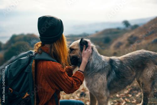 kobieta głaszcze psa w podróży góry