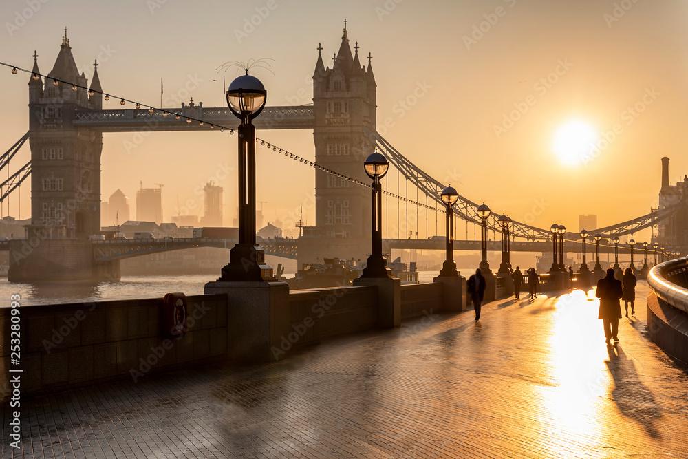 Wschód słońca nad Tower bridge w Londynie z sylwetkami ludzi idą do pracy