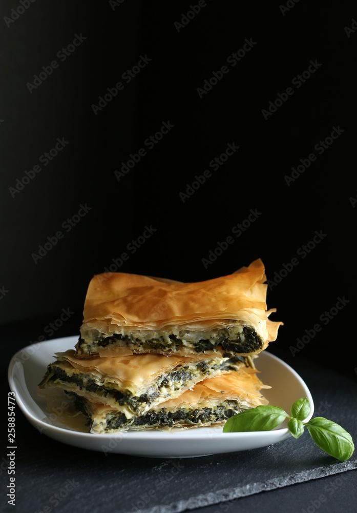Dania kuchni greckiej. Spanakopita na czarnym tle