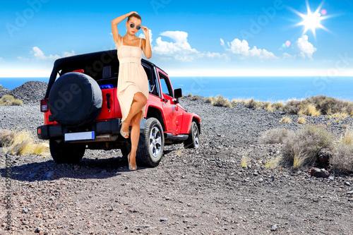 Szczupła, młoda kobieta z czerwony samochód i krajobraz
