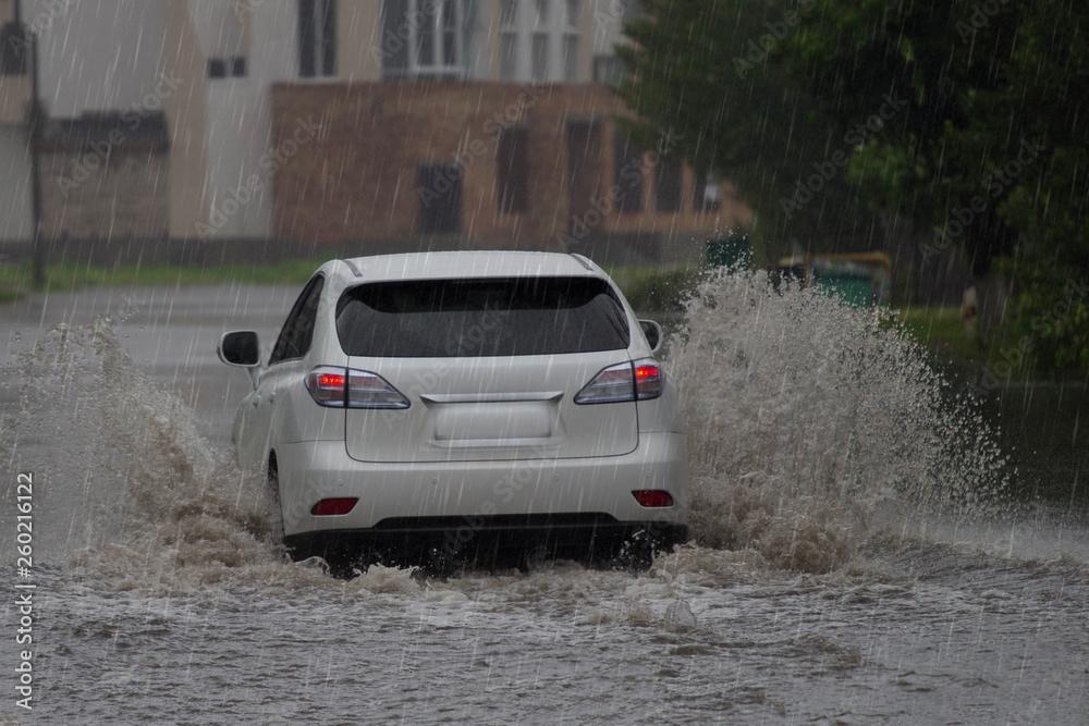 samochód jedzie w deszczu na zalane drogi