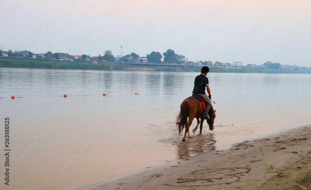 Młody człowiek jeździ na koniu na plaży na brzegu rzeki