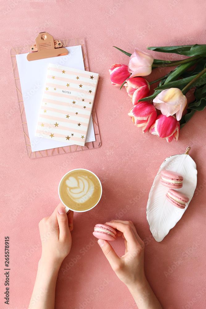 Kobieta ręce kubek, trzymając kawę z francuskimi słodyczami. Widok z góry strzał w fmale mieć gorący napój z latte art pianka i makaroniki deser ciasto. Zbliżenie, kopia przestrzeń, w tle.