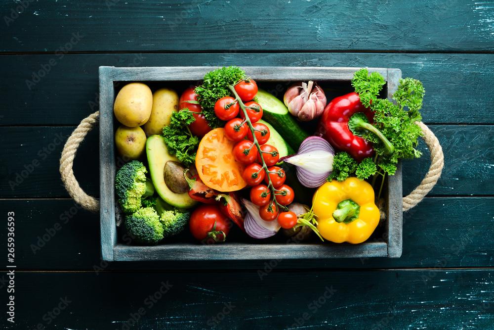 Świeże warzywa i owoce w drewnianej skrzyni. Awokado, pomidory, truskawki, melon, ziemniaki, papryka, owoce cytrusowe. Widok z góry. Ilość wolnego miejsca dla tekstu.