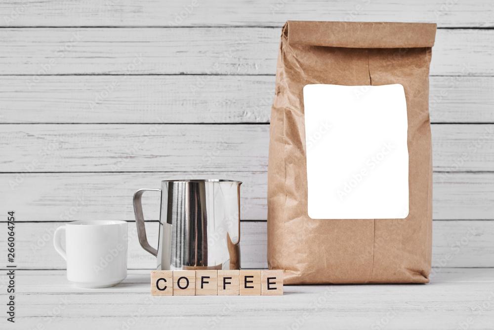 Filiżanka kawy, rzemiosło papierową torbę i dzbanek ze stali nierdzewnej na białym tle, miejsce