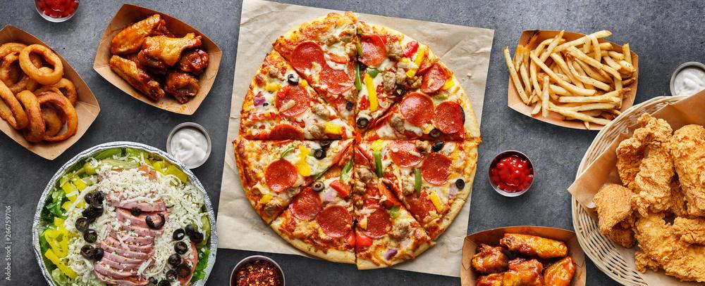 duży stół z różnych produktów, takich jak pizza, frytki, krążki cebulowe, smażone kurczaki i skrzydełka z kurczaka