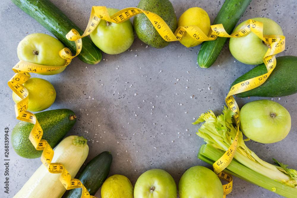 świeże zielone warzywa i owoce z miara na szarej powierzchni ,ogórki, jabłka, truskawki, seler, cytryna, awokado