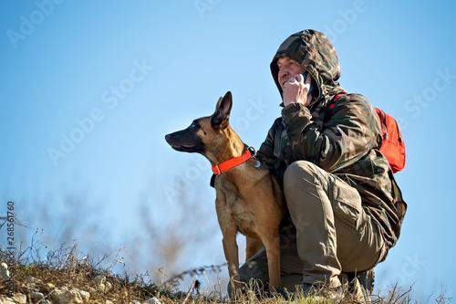 Człowiek na spacerze mówi przez telefon komórkowy i przytula psa