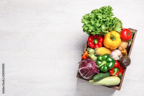 Pudełko z różnymi świeżymi warzywami na jasnym tle, widok z góry. Miejsca na tekst