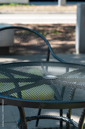 Metal table with a glass top and an openwork metal garden chair