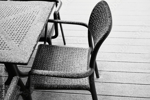 abstract snow-covered parts of the chair and table of black color and closeup outdoors with white snow