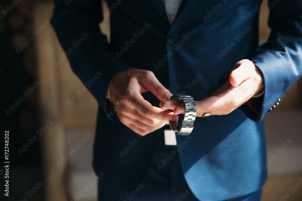 Mężczyzna w niebieskiej kurtce z tuxedo nosić zegarek. Pojęcie biżuteria, sukienka