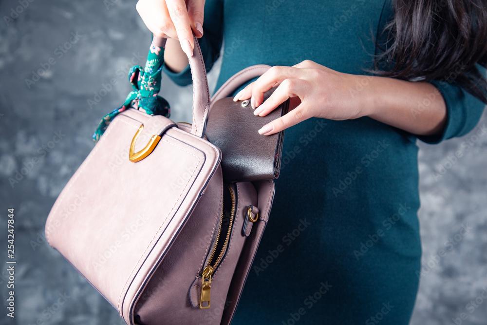 kobieta ręką portfel z workiem na ciemnym tle