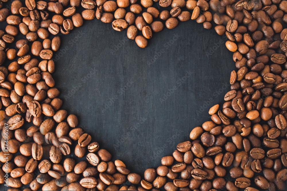 Ziarna kawy w kształcie serca na czarnym drewnianym tle. Kawa serce