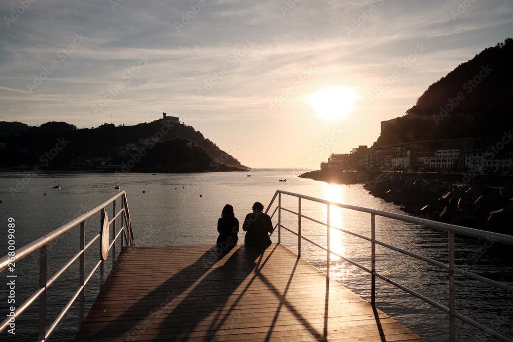 Hiszpania, San Sebastian 14 maja 2019 para cieszy się zachód słońca w przedniej części zatoki La Concha w San Sebastian.