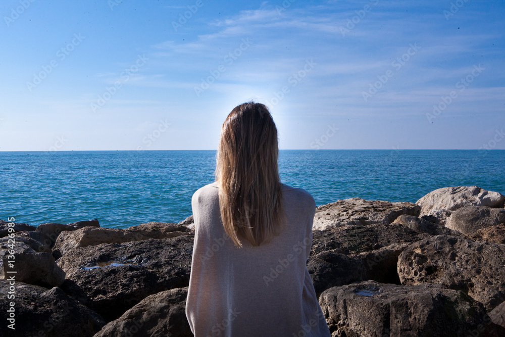 kobieta siedzi plecami o skały i patrzy na morze