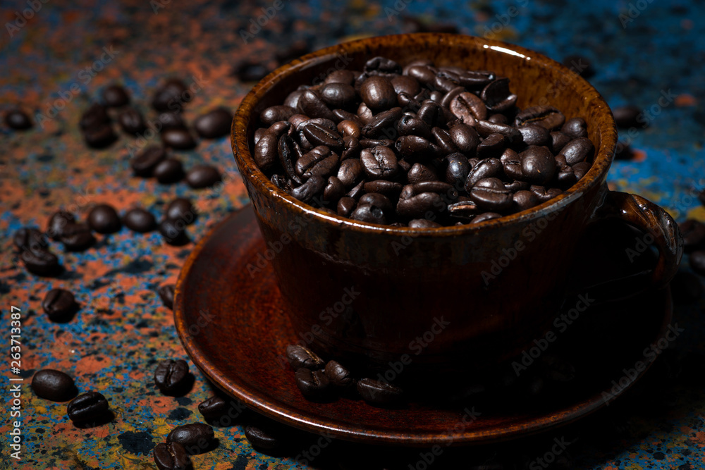 filiżanka z ziaren kawy na ciemnym stole