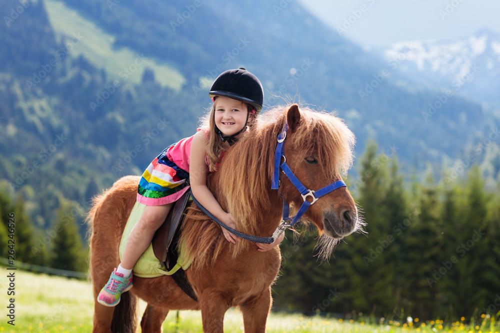Dzieci, jazda na kucyku. Dziecko na koniu w górach Alpach